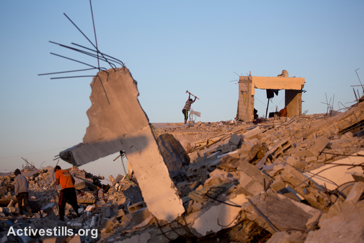 Palestinians salvage materials from destroyed homes in the village of Khuza'a, eastern Gaza Strip, November 6, 2014. Many Palestinians in the Gaza Strip face hard living conditions following the seven-week Israeli offensive during which 2,131 Palestinians were killed, and an estimate of 18,000 housing units have been either destroyed or severely damaged, leaving more than 108,000 people homeless. (photo: Activestills.org)