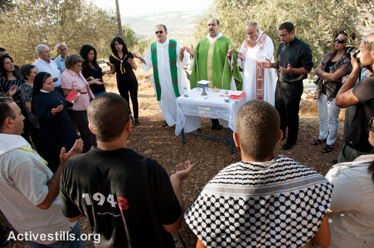 Palestinians hold a Catholic mass as a weekly nonviolent witness against the Israeli separation wall in the West Bank village of Beit Jala, September 7, 2012. If completed as planned, the wall would cut off the Cremisan monastery from the Beit Jala community, blocking access to one of the Bethlehem area's last remaining green spaces, and a source of employment for area residents. (photo: Ryan Rodrick Beiler/Activestills.org)
