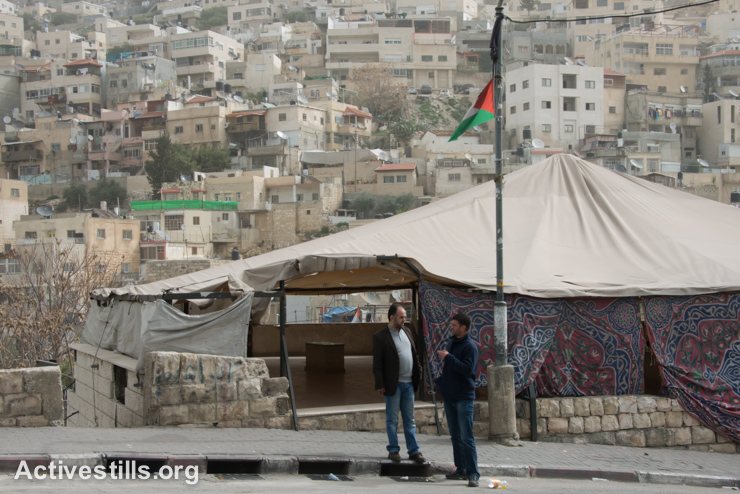 Daoud Al-Ghould talks with a neighbor of the East Jerusalem neighborhood of Silwan stand near a protest tent built by local activists, March 3, 2014. (photo: Ryan Rodrick Beiler/Activestills.org)