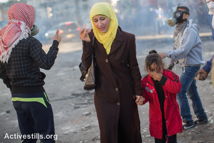 A Palestinian woman and her daughter run to take cover during clashes with Israeli border police at the checkpoint separating Shuafat refugee camp from Jerusalem, November 6, 2014. (photo: Activestills.org)