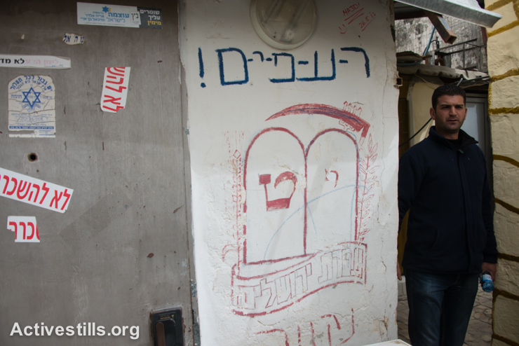 Daoud Al-Ghoul walks near graffiti painted by Israelis on properties taken over by settlers in the Muslim Quarter of Jerusalem's Old City, March 3, 2014. Many of these properties taken over by settlers are as small as a single room directly adjacent to Palestinian homes.