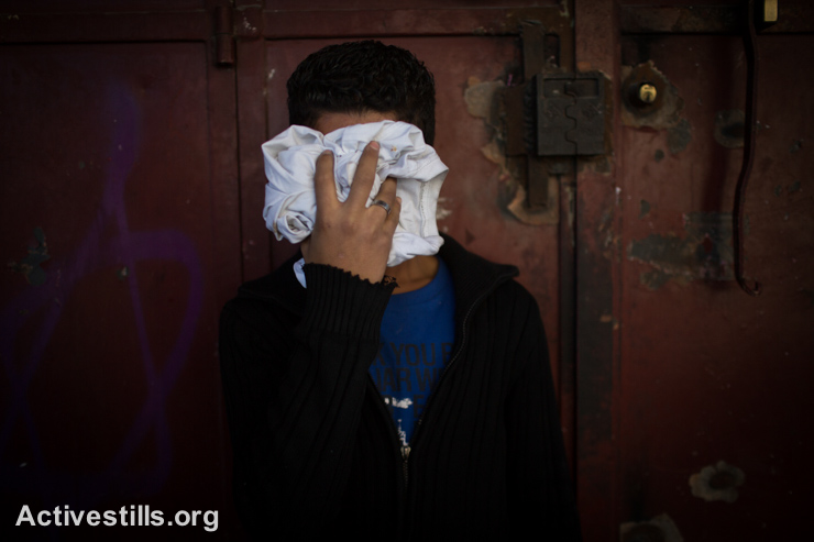 A Palestinian youth cover his face to avoid tear gas, during clashes of Palestinian youth with Israeli border police at a checkpoint between Shuafat refugee camp and Jerusalem, November 7, 2014. Clashes broke after a Palestinian man drove a car into a crowd, killing a policeman and injuring 13 people in Jerusalem on November 5. (photo: Activestills.org)
