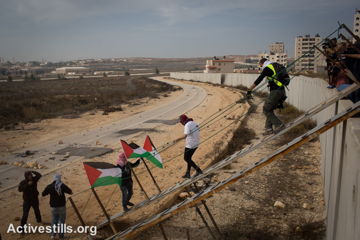 Palestinian activists use a metal ramp to cross the separation wall near the Israeli Qalandiya checkpoint between the West Bank city of Ramallah and Jerusalem, November 14, 2014. The activists were protesting against Israeli authorities allowing settlers to enter the compound surrounding Al-Aqsa Mosque and the imposition of restrictions on Muslims wishing to perform Friday prayers there. (photo: Activestills.org)