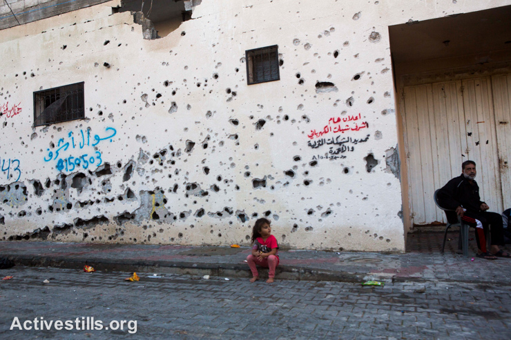 A Palestinian child sits in front of a wall riddled with shrapnel, in the city of Beit Hanoun, Gaza Strip on November 17, 2014. (photo: Activestills.org)