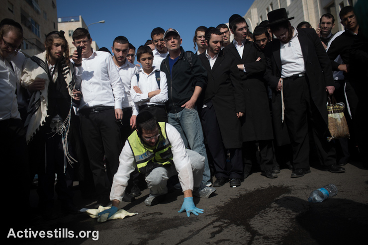 Israeli emergency services members clean the sidewalk at the scene of an attack by two Palestinians on Israeli worshippers at a synagogue in the ultra-orthodox Har Nof neighborhood in West Jerusalem, November 18, 2014. Two Palestinians armed with a gun and meat cleavers burst into a Jerusalem synagogue and killed four worshippers and mortally wounded a policeman before being shot dead by Israeli police. (photo: Activestills.org)