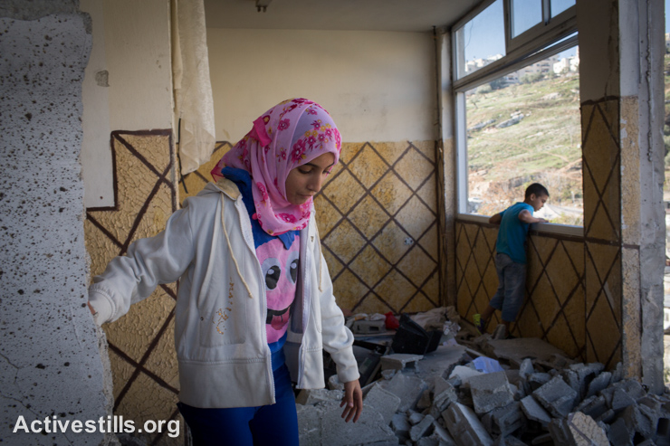 Family members of Abdel Rahman Al-Shaludi, a Palestinian who drove his car into passengers at a rail station causing the death of two Israelis last month in Jerusalem, inspect his destroyed apartment in the East Jerusalem neighbourhood of Silwan, November, 19, 2014. The previous night, Israeli army and police destroyed the apartment of Al-Shaludi, as the Israeli government ordered the demolition of homes of Palestinians who carry out attacks against Israelis. (photo: Activestills.org)