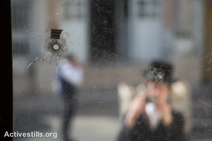 An ultra-orthodox Jewish man looks at bullet holes in a window inside a synagogue that was attacked a day before by two Palestinians in the ultra-orthodox Har Nof neighbourhood in West Jerusalem, November 19, 2014.  (photo: Activestills.org)