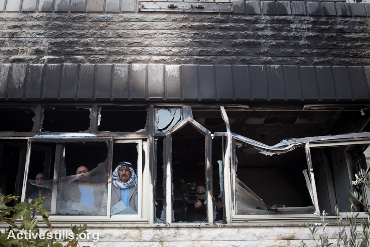 A Palestinian man inspects the damage inside the Abu Ranni family home, which was attacked and burned by suspected Jewish extremists using petrol bombs in the village of Abu Falah, northeast of Ramallah, West Bank, November 23, 2014. (photo: Activestills.org)