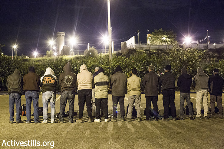 Palestinian laborers pray outside the Sha'ar Ephraim checkpoint separating the West Bank and Israel, December 22, 2014. (Oren Ziv/Activestills.org)
