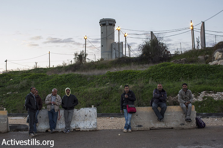 Palestinian laborers wait outside the Sha'ar Ephraim checkpoint separating the West Bank and Israel for their Israeli employers to pick them up, December 22, 2014. (Oren Ziv/Activestills.org)