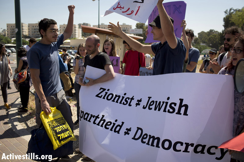 Israeli activists take part in a protest as Uriel Ferera, a 19-year-old Orthodox Jew from Beer Sheva, enters the Tel Ha'Shomer Military Base, where he would announce his refusal to draft to Israeli army service, April 27, 2014. Uriel spent 177 days in military prison and was finally released on December 21, 2014. By: Oren Ziv/Activestills.org   For more on Uriel Ferera and contentious objectors in Israel, click here.
