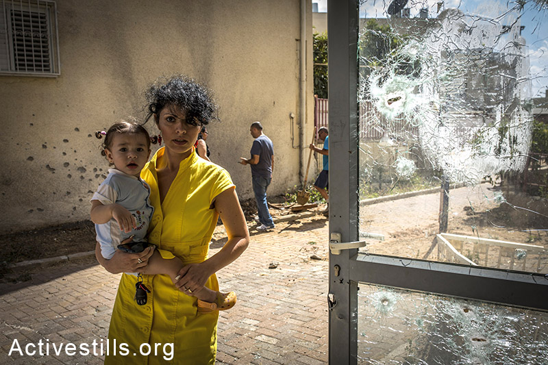 A woman and her baby standing near an area hit by a missile launched from Gaza in the town of Sderot, Israel, on July 15, 2014. By: Yotam Ronen/Activestills.org   Read more on the impact of the war on Israel's southern residents here, and the political changes it led to in the political echelon here.
