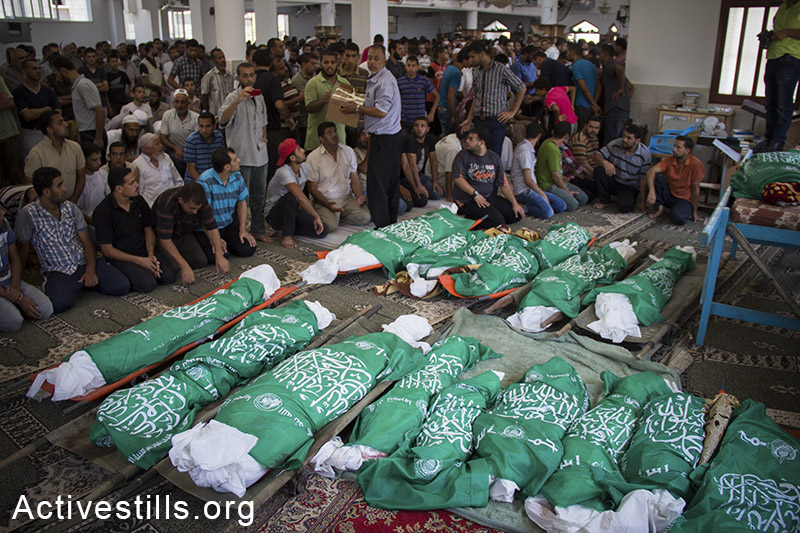 Mourners at the funeral for the 26 members of the Abu Jame' family, who were killed the previous day during an Israeli attack over the Bani Suhaila neighborhood of Khan Younis, Gaza Strip, July 21, 2014. Reports indicatde that 18 of the 24 killed were children of Abu Jame' family. Israeli attacks killed over 2,100 Palestinians in the offensive, a majority of them civilians. Basel Yazouri/Activestills.org   Read +972's 'Story of the Year': Gaza.