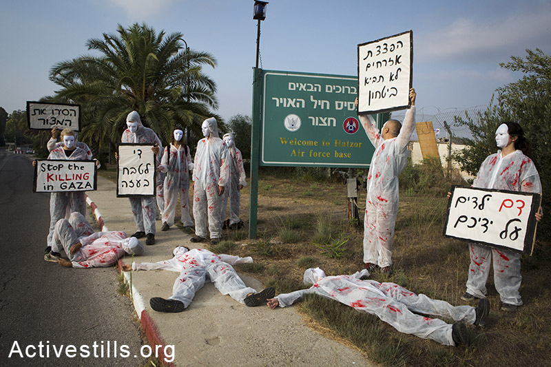 """Israeli women activists stage a protest against the attack on Gaza at Hatzor Air Force base, Israel, July 29, 2014. The activists wore white overalls stained with red paint calling on the Israeli government to stop the strikes and bring an end to the siege on Gaza, also expressing concern regarding the suffering of civilians in southern Israel. Signs in Hebrew read (from R to L): """"The blood of children is on your hands""""; """"Bombing civilians will not bring security""""; """"Stop the massacre in Gaza"""" and """"Remove the siege"""". A few activists were detained by security forces. By: Keren Manor/Activestills.org   Read more on the backlash to anti-war protests here, and +972's Story of the Year: Gaza, here."""