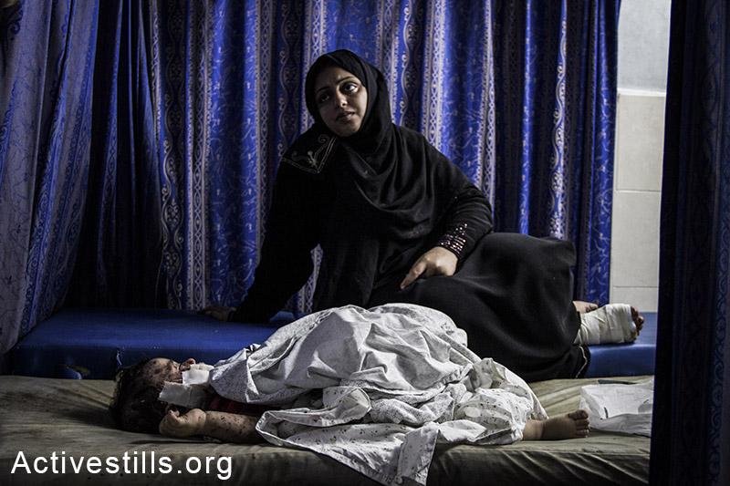An injured Palestinian child awaits treatment at Al Shifa Hospital in Gaza City following Israeli attacks, July 30, 2014.. By: Basel Yazouri/Activestills.org   Read +972's 'Story of the Year: Gaza'