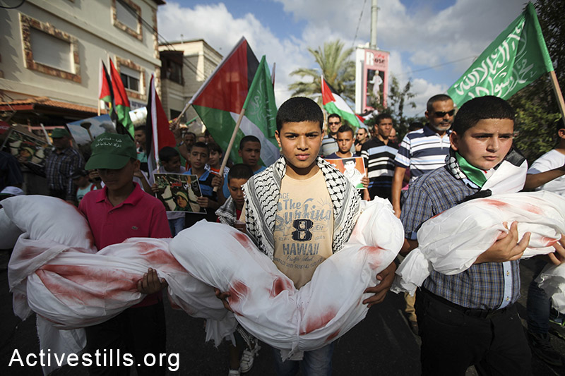 Palestinian youth living in Israel hold dolls wrapped in a white cloths, during a demonstration against the Israeli attack on Gaza and in support of the Palestinian people, in the northern village Tamra on August 2, 2014. By: Faiz Abu-Rmeleh/Activestills.org   Read more on Palestinian protests against the war inside Israel here, and +972's Story of the Year: Gaza, here.