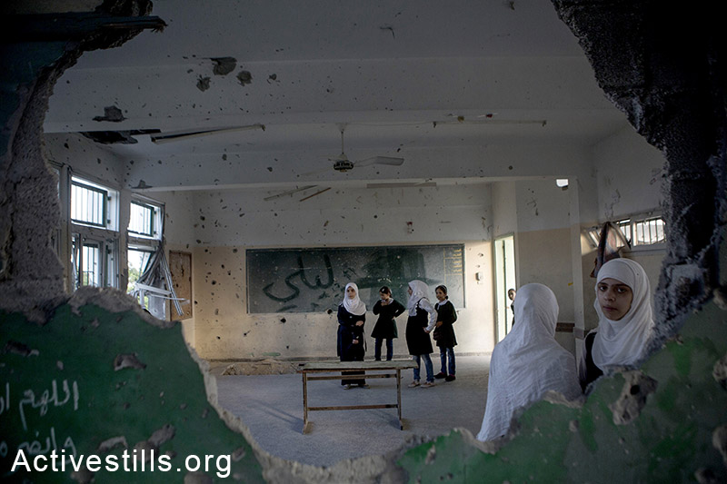 Palestinian school students stand in a destroyed classroom in the damaged Sobhi Abu Karsh basic-school in a destroyed quarter of the Shujayea neighborhood, Gaza city, September 15, 2014. The school year started with a three-week delay, due to the latest Israeli offensive. During the attack 29 schools were destroyed, and around 190 were damaged. An estimated 18,000 housing units were either destroyed or severely damaged, leaving more than 108,000 people internally displaced. By: Anne Paq/Activestills.org   Read more on the start of the post-war school year here and on internally displaced Gazans here.