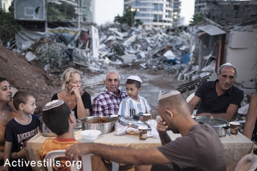 The Kadoori, Hamias and Ashram families sit near an improvised Shabat dinner table set near their demolished houses in Givat Amal neighbourhood, Tel Aviv, Israel, September 19, 2014. Two days passed since the third eviction of families in the neighbourhood which left 20 residents homeless without proper compensation or alternative housing solution. By: Shiraz Grinbaum/Activestills.org