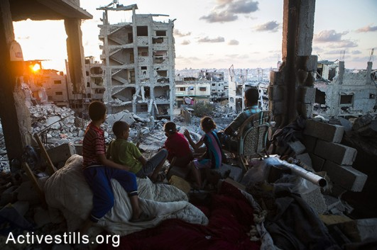 A Palestinian family sits in their destroyed home in a quarter in At-Tuffah district of Gaza city, which was heavily attacked during last Israeli offensive, Gaza city, September 21, 2014. (Photo: Anne Paq/Activestills.org)