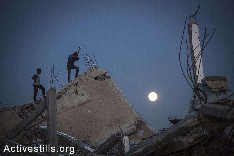 Palestinians salvage materials from destroyed homes in the village of Khuza'a, eastern Gaza Strip, November 6, 2014. (Anne Paq/Activestills.org)