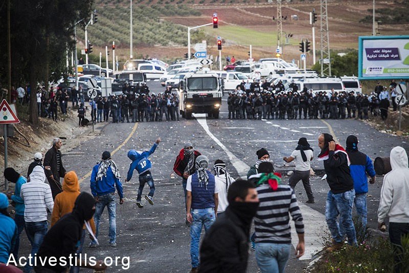 Arab youth throw stones during clashes with the Israeli police in the entrance to the town of Kfar Kanna, in the north of Israel, November 8, 2014. Clashes broke after police shot and killed of 22-year-old Khayr al-Din al-Hamdan, that was approaching a police car with a knife, during a police raid in the village the night before. By: Oren Ziv/Activestills.org