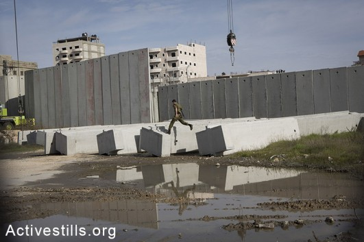 An Israeli soldier jump as a construction vehicle places a concert part of the Israeli Separation Wall in the Shuafat refugee camp in East Jerusalem, December 3, 2014. (Oren Ziv/Activestills.org)