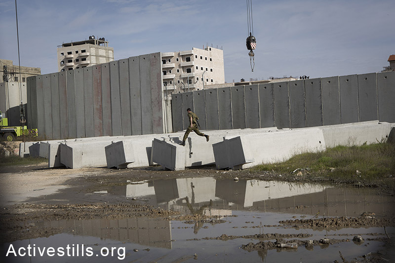 An Israeli soldier jumps as a construction vehicle places a part of the Israeli Separation Wall in the Shuafat refugee camp in East Jerusalem, on December 3, 2014. The Israeli authorities, under the supervision of Israeli security forces, destroyed Palestinian owned shops that were built without a permit, clearing space for a new parking lot for the Shuafat checkpoint. Palestinians in the East Jerusalem neighborhoods rarely receive building permits due to the municipality's discriminative policies. By: Oren Ziv/Activestills.org   Read more on the Shuafat refugee camp here.