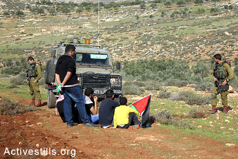 Palestinian farmers detained after sowing their lands located behind a settlers' by-bass road, at Salem village, Nablus, West Bank, December 05, 2014.  Photo by: Ahmad al-Bazz/Activestills.org
