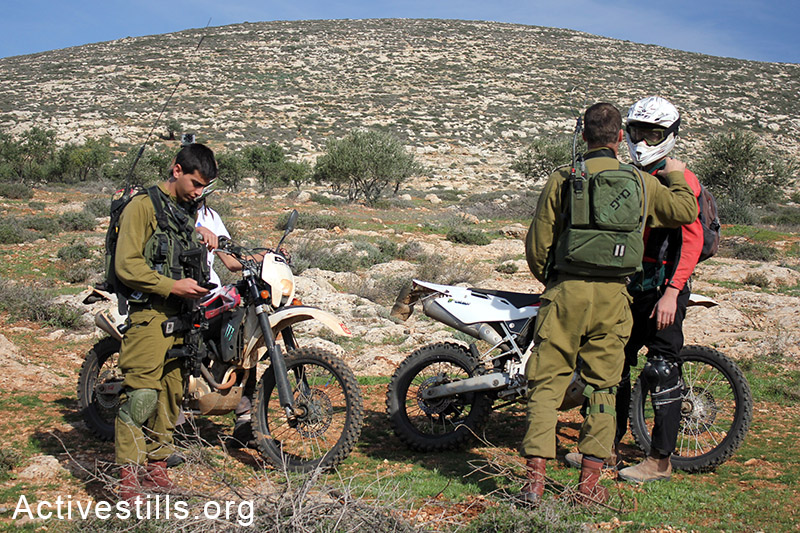 Israeli settlers try to provoke Palestinian framers by driving their motorcycles among the group, Salem village, Nablus, West bank, 5.12.2014. Photo by: Ahmad al-Bazz/Activestills.org