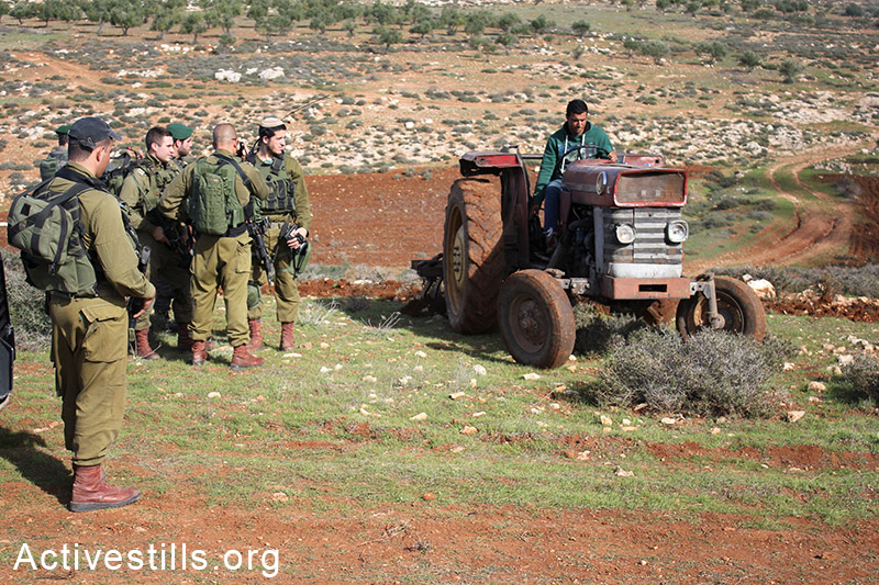 Israeli soldiers watch as Palestinian farmers sow their lands located behind a settlers' by-bass road, at Salem village, Nablus, West Bank, December 05, 2014.  Photo by: Ahmad al-Bazz/Activestills.org