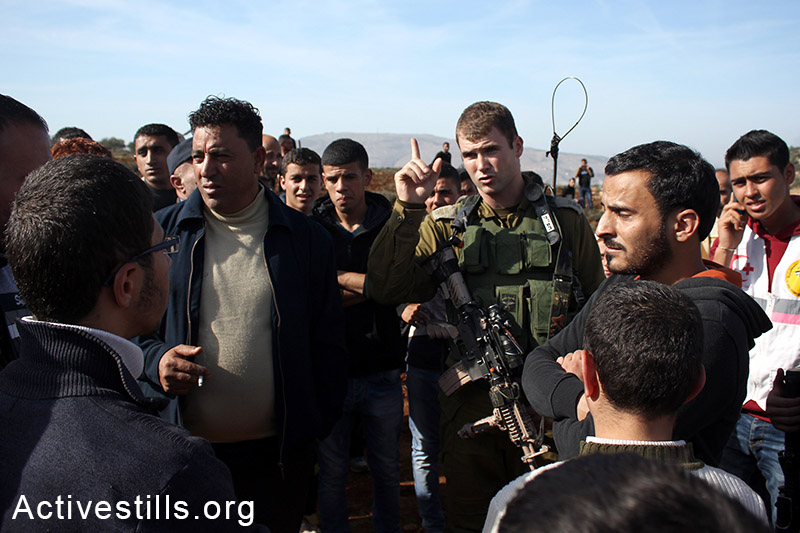 Palestinian farmers argue with Israeli soldiers who try to prevent them from sowing, Salem village, Nablus, West Bank, December 5, 2014. Photo by: Ahmad al-Bazz/Activestills.org