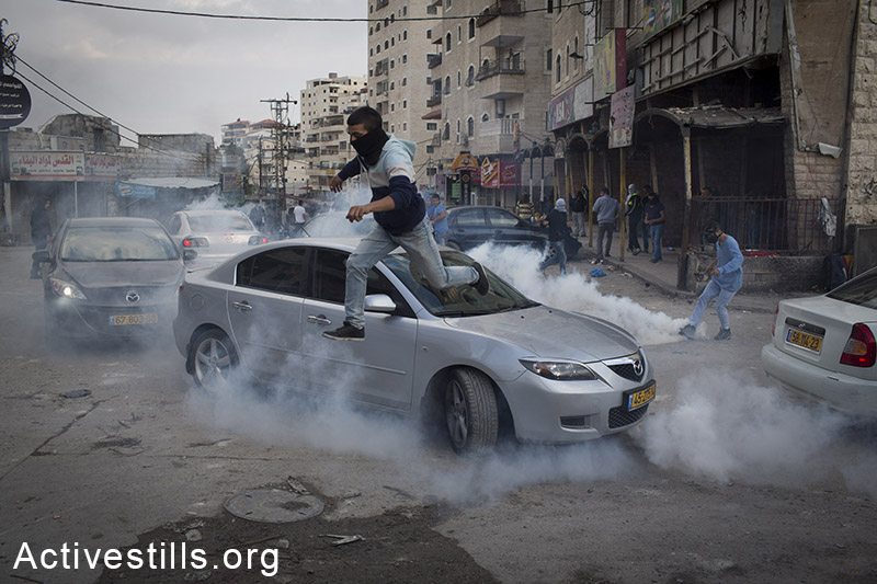 A Palestinian runs to take cover from tear gas, during clashes with Israeli police at the Palestinian refugee camp of Shuafat in East Jerusalem, November 5, 2014. Clashes broke after a Palestinian man drove a car into a crowd, killing a policeman and injuring 13 people in Jerusalem. By: Oren Ziv/Activestills.org