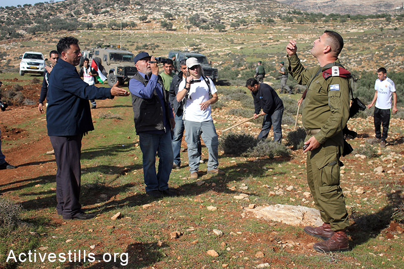 Palestinian farmers argue with Israeli soldiers who try to prevent them from sowing, Salem village, Nablus, West Bank, December 5, 2014.