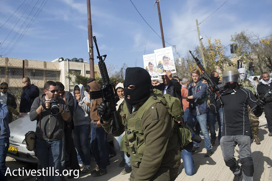 Members of the Al-Aqsa Martyr's Brigade fire into the air during Ziad Abu Ein's funeral procession, December 11, 2014. (photo: Oren Ziv/Activestills.org)
