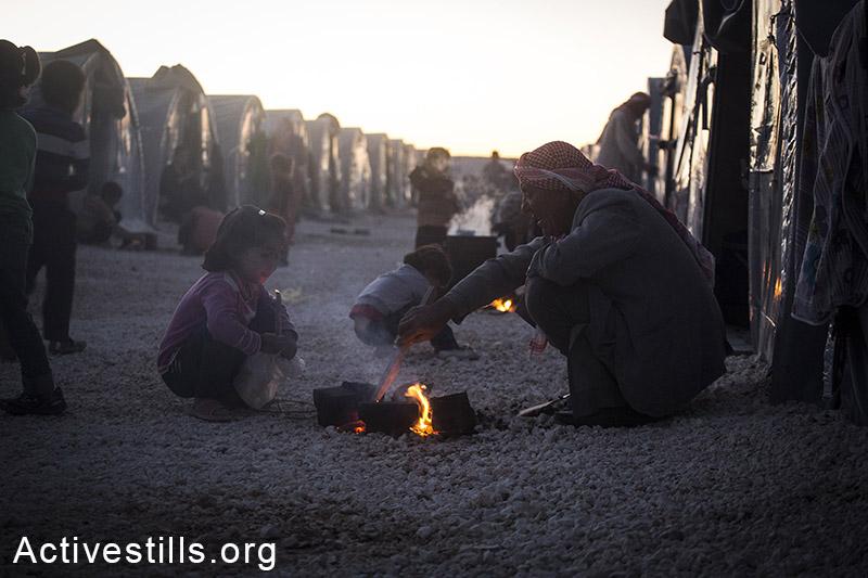 Refugees warm up near a fire at Arin Mirxan refugee camp, October 2014. Photo: Faiz Abu-Rmeleh/Activestills.org