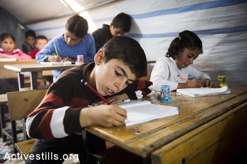 Children study at a volunteer-run school at Ravaya refugee camp, Suruc, Turkey, October 2014. Photo: Faiz Abu-Rmeleh/Activestills.org