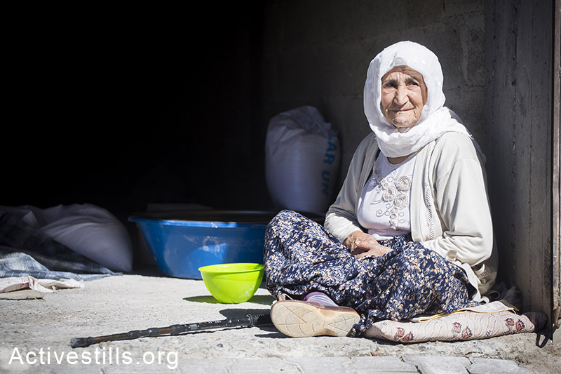 A refugee who fled the Syrian city of Kobane sits in a makeshift shelter, Suruc, October 2014. Photo: Faiz Abu-Rmeleh/Activestills.org