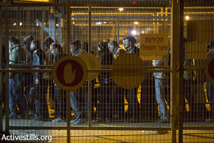 Palestinian laborers arrive at the first of eight metal carousels they must pass through in the Sha'ar Ephraim checkpoint separating the West Bank and Israel, December 22, 2014. (Oren Ziv/Activestills.org)