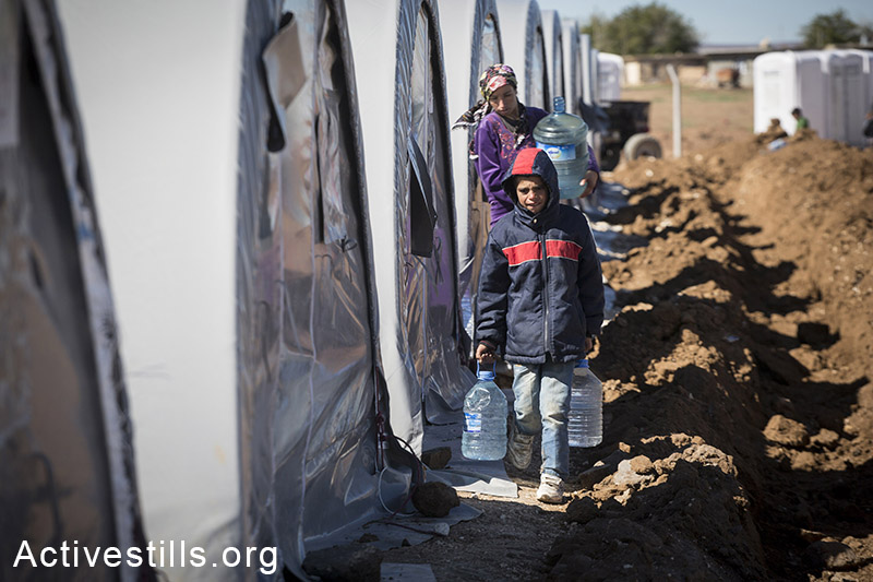 A family carries water in Arin Mirxan refugee camp, October 2014. Photo: Faiz Abu-Rmeleh/Activestills.org