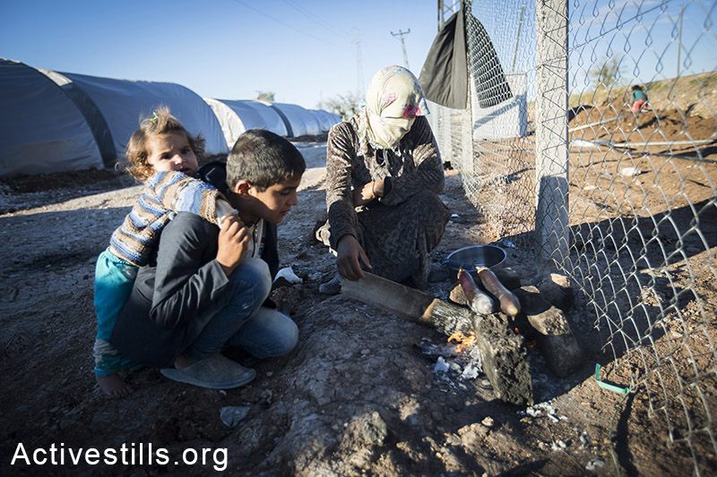 A family cooks together in Arin Mirkhan refugee camp, October 2014. Photo: Faiz Abu-Rmeleh/Activestills.org