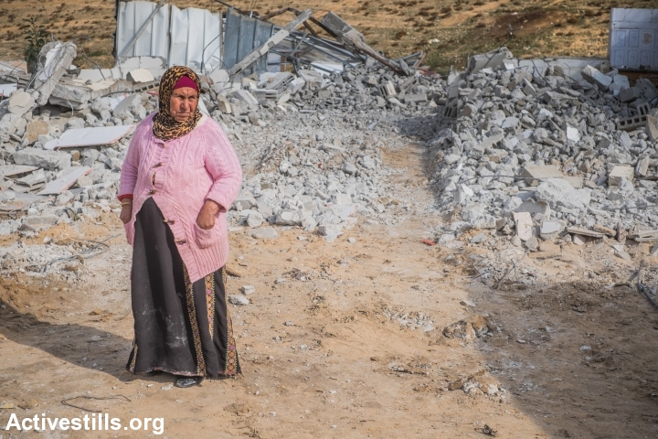 A Bedouin woman is seen near the ruins of her house in the unrecognized Bedouin village of Sawa, after her family demolished the house to prevent Israeli authorities from doing it themselves, Negev Desert, December 23, 2014. (Yotam Ronen/Activestills.org)