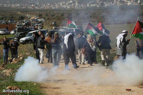 Israeli troops shoot tear gas at Palestinian demonstrators protesting the illegal outpost of Adei Ad in the northern West Bank, December 10, 2014. (Photo by Oren Ziv/Activestills.org)