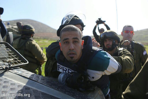 Israeli troops detain a Palestinian journalist at a protest against the illegal settlement outpost of Adei Ad in the northern West Bank, December 10, 2014. The journalist was later released. (Photo by Oren Ziv/Activestills.org)