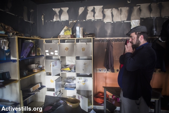 A teacher looks at the damage in a first-grade classroom at one of Jerusalem's only integrated Jewish-Arab schools, which was the target of an ideologically motivated arson attack, November 30, 2014. (Photo by Oren Ziv/Activestills.org) One of the suspects is being represented by Honenu.