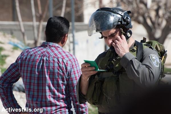 Israeli border police check the ID of a Palestinian man (File photo by Ryan Rodrick Beiler/Activestills.org)