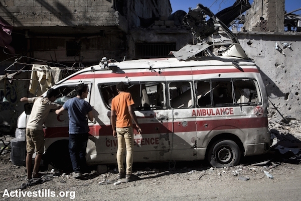 Palestinians inspect damage to a destroyed ambulance in Shujaiyeh, a neighborhood in eastern Gaza City that was the site of some of the war's heaviest fighting, July 27, 2014. (Photo by Anne Paq/Activestills.org)