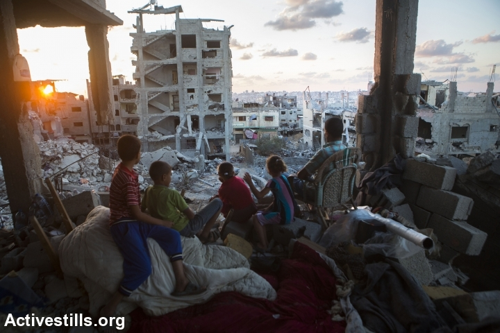 A Palestinian family sits in their destroyed home in the at-Tuffah district of Gaza City, which was heavily attacked during summer's Israeli offensive, September 21, 2014. An estimated 18,000 housing units were destroyed or severely damaged, leaving more than 108,000 people homeless. (Photo by Anne Paq/Activestills.org)
