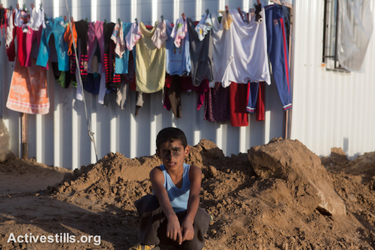 A Palestinian child with ash on his face sits in one of the newly established camps with metal caravan shelters for displaced people in the village of Khuza'a, eastern Gaza Strip, November 9, 2014. (photo: Activestills.org)