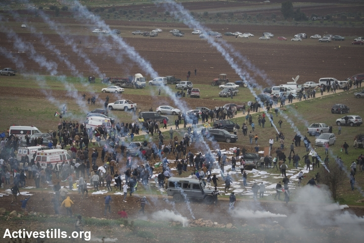 Palestinians run to take cover, as the Israeli army shoot tear gas, during a demonstration commemorating the death of Palestinian minister, Ziad Abu Ein, in the West Bank village of Turmus Aya, north of Ramallah, December 19, 2014. (photo: Oren Ziv/Activestills.org)