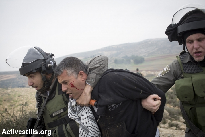 Israeli border policemen arrest Palestinian activist Muhammad Khatib during a demonstration commemorating the death of Palestinian minister, Ziad Abu Ein, in the West Bank village of Turmus Aya, north of Ramallah, December 19, 2014. (photo: Oren Ziv/Activestills.org)